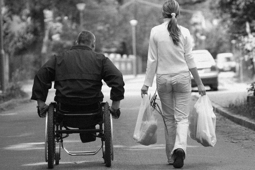 man in wheelchair and woman walking beside him