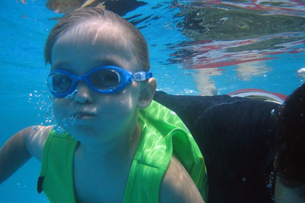 child underwater holding breath