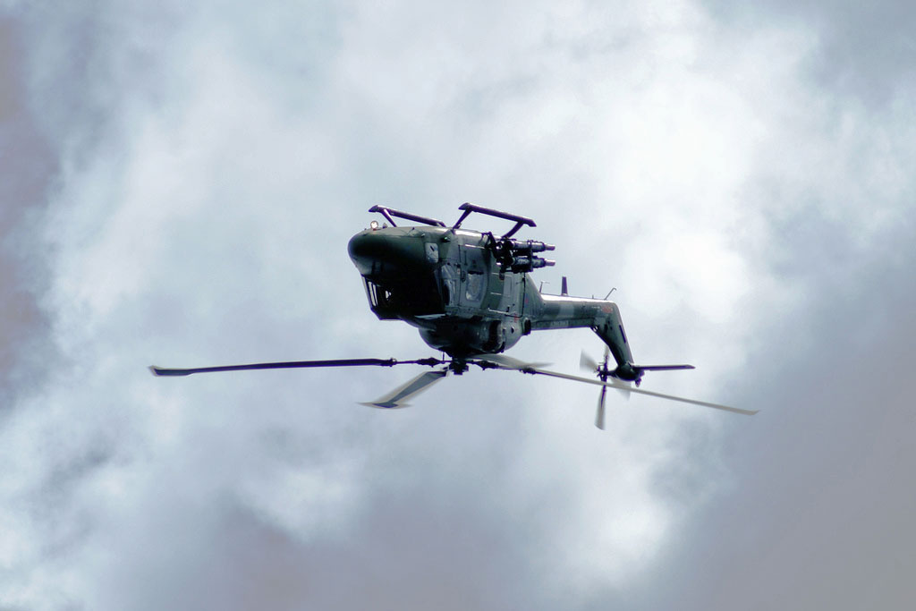 helicopter upside down in the sky with clouds in the background