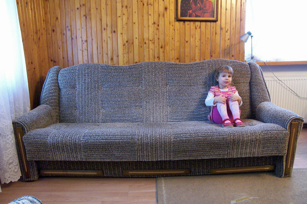 girl sitting on the far right of a gray couch