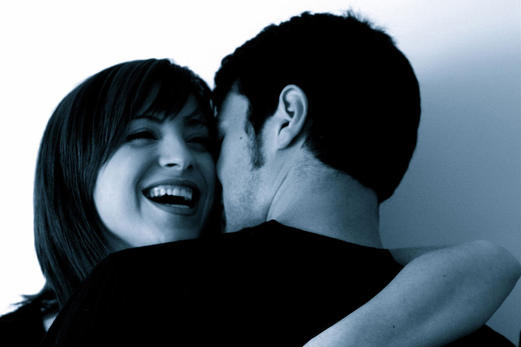 woman smiling while hugging a man in black and white