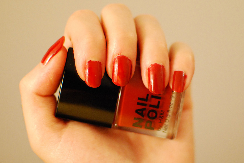 hand holding bottle of red nailpolish with nails painted red