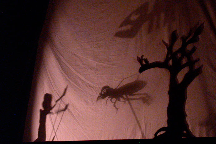 Scene from a shadow puppet play featuring scary flying creatures.