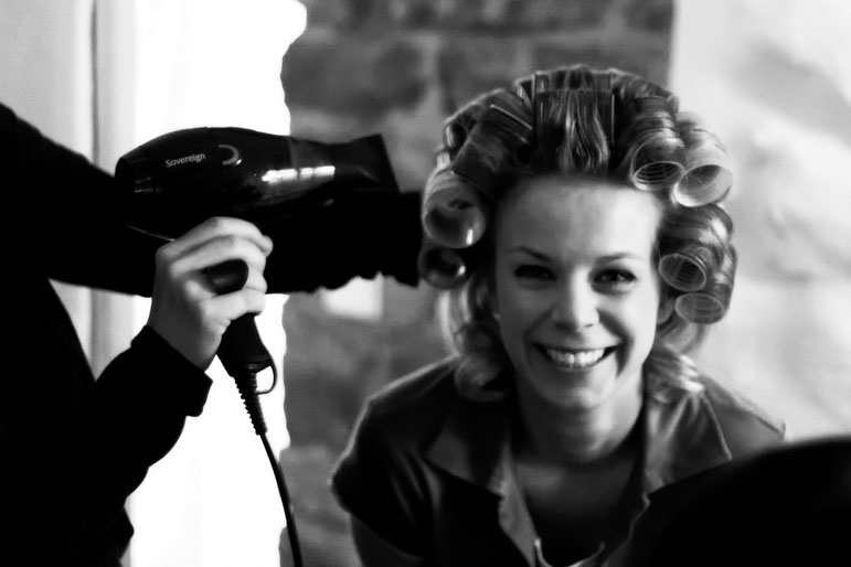 A hair stylist works to achieve a perfect head of curls.