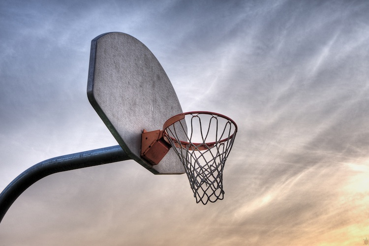 An outdoor basketball hoop at sunset