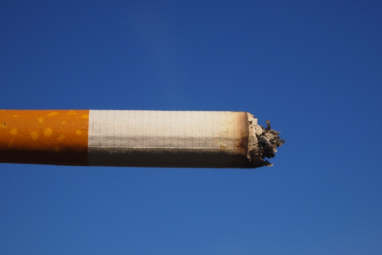 A cigarette burns against blue sky