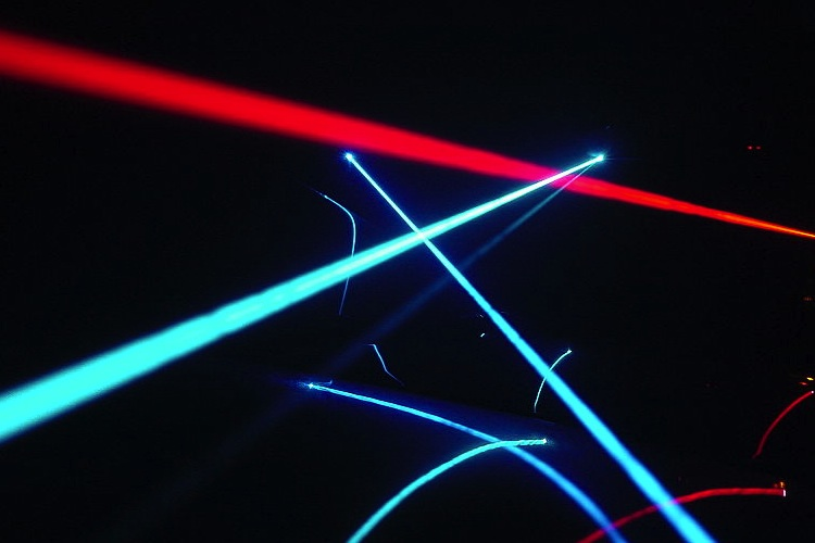 Different colored laser beams intersect in the darkness