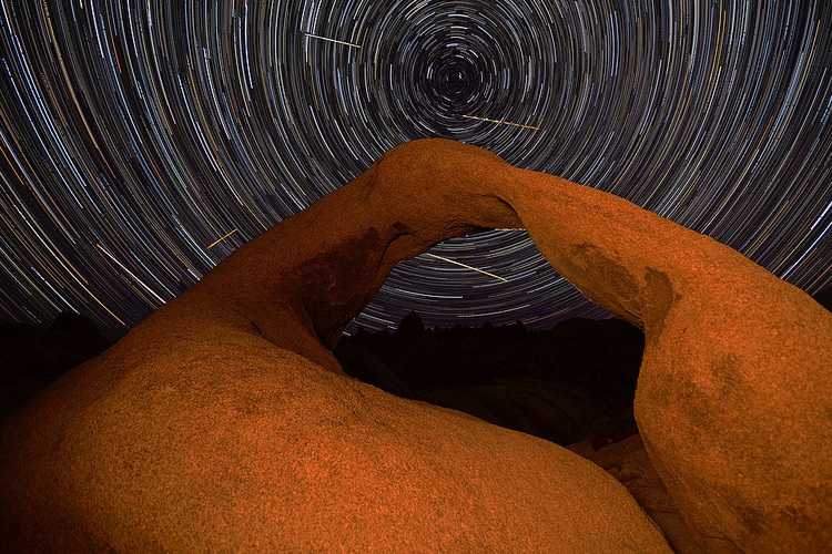 Time-lapse photo of a natural arch at night with a few meteors streaking in the starry sky behind