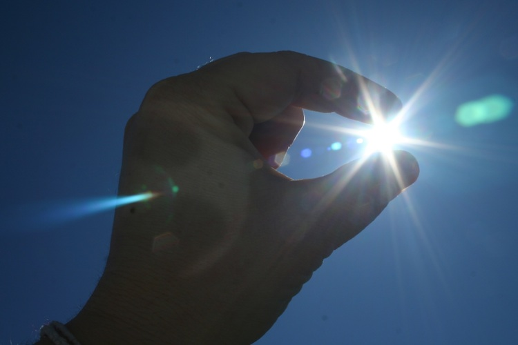Fingers appear to pinch the sun