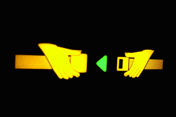 """A yellow """"fasten seatbelt"""" sign"""