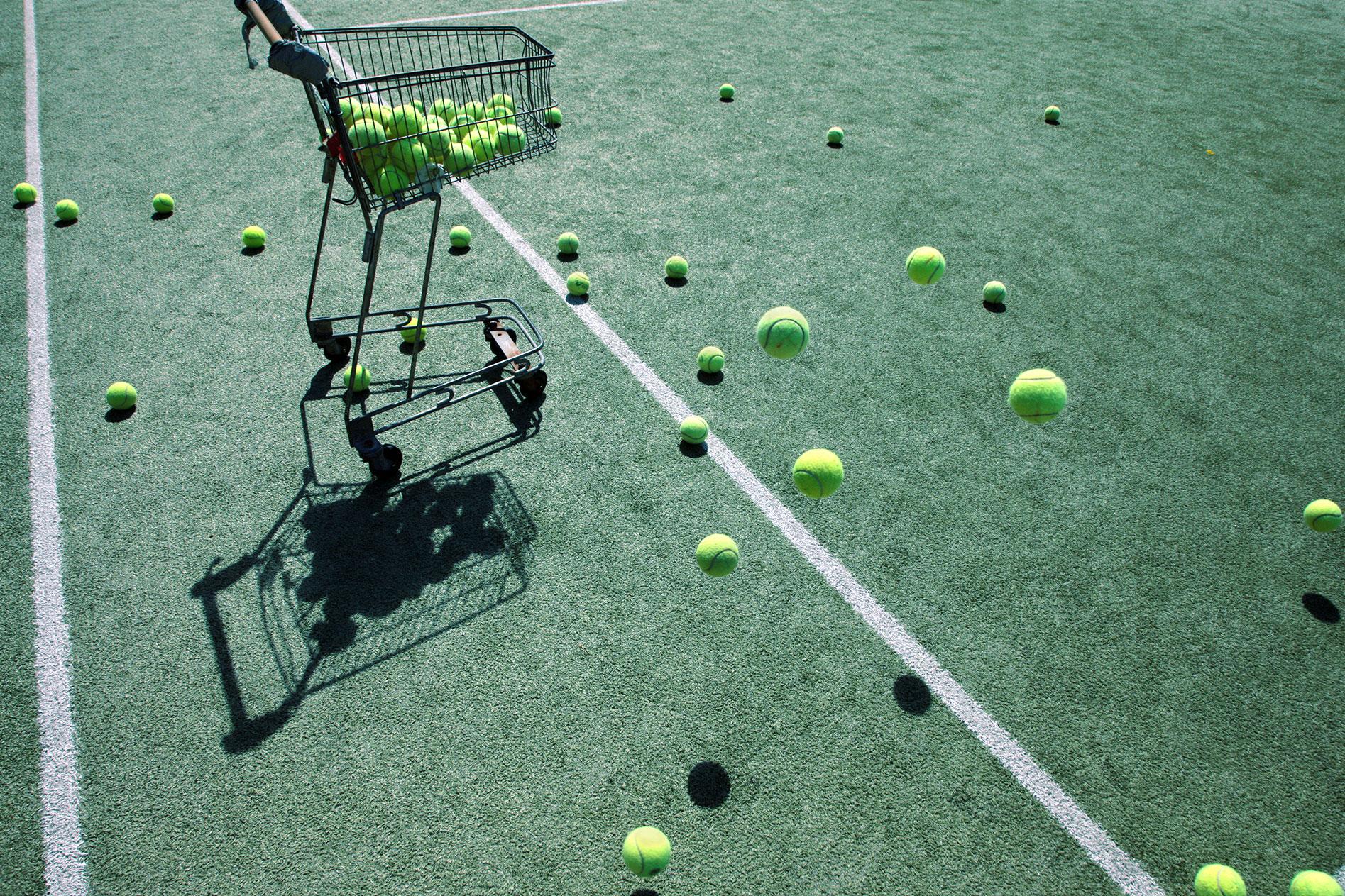 A cart full of tennis balls on a tennis ball court
