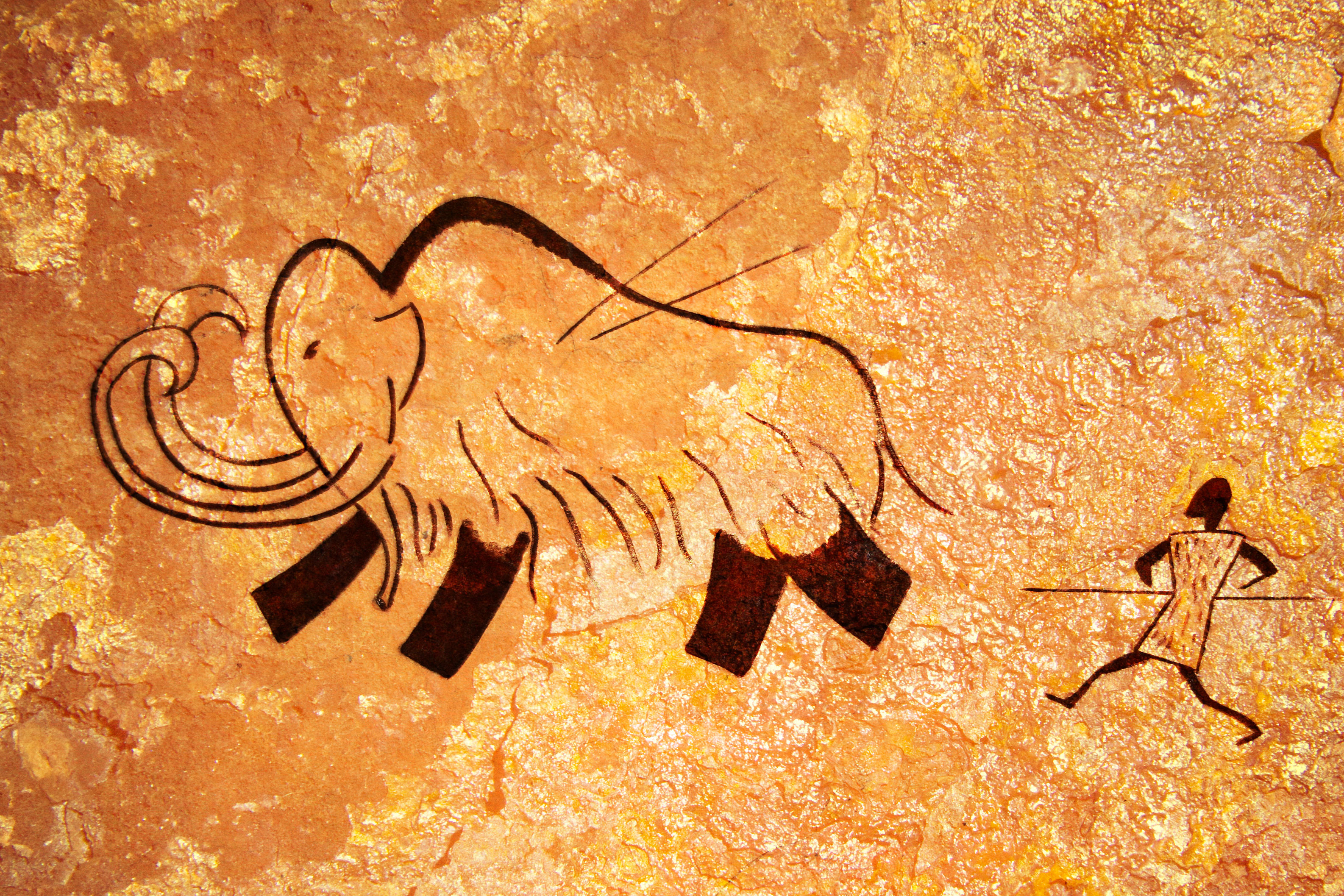 Cave painting of a hunter spearing a wooly mammoth