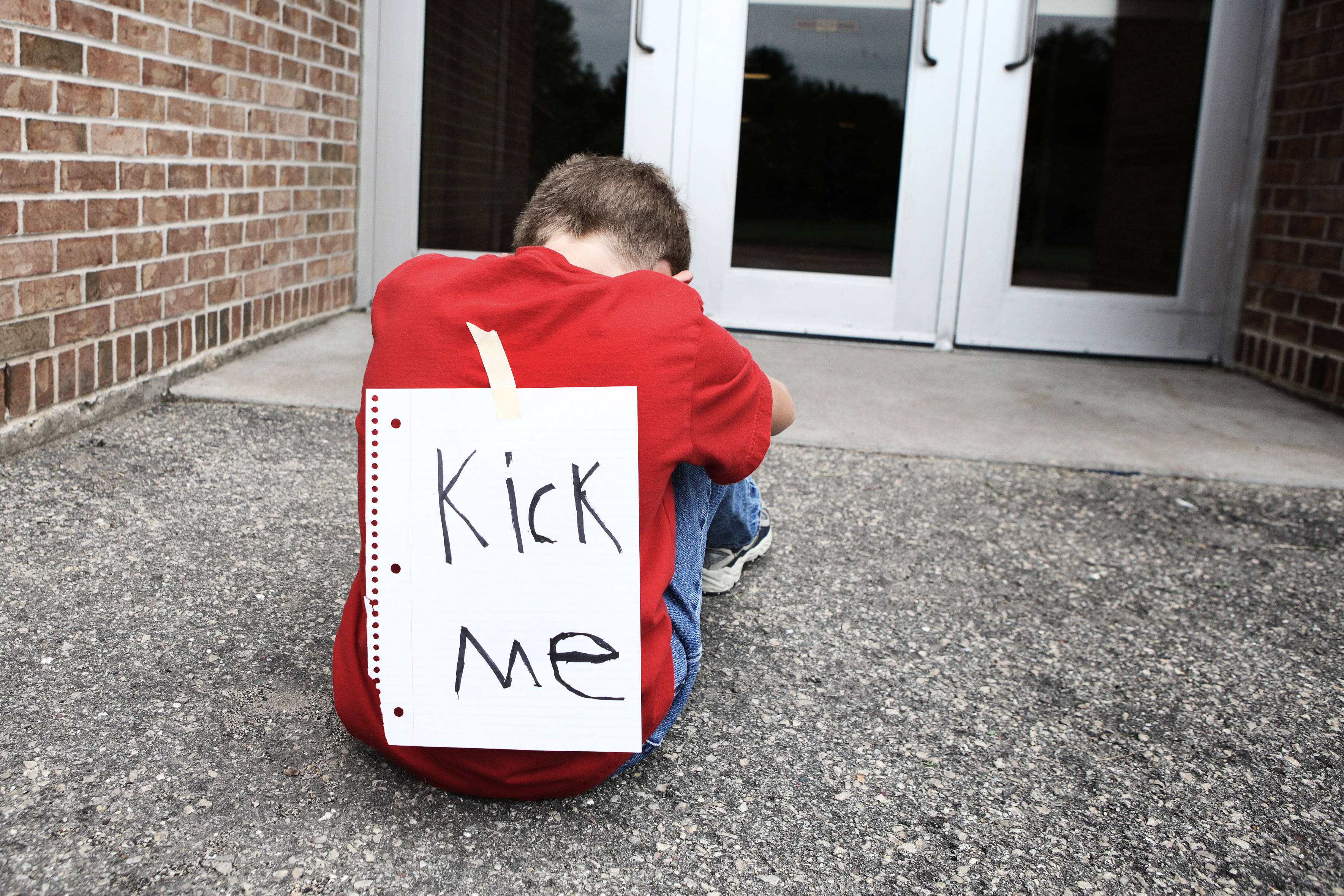 """child with """"Kick Me"""" sign"""