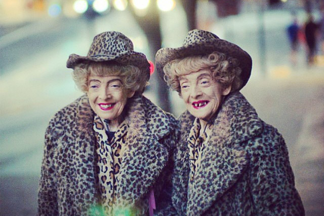 Older women who are twins. They are dressed in similar leopard print coats and hats.