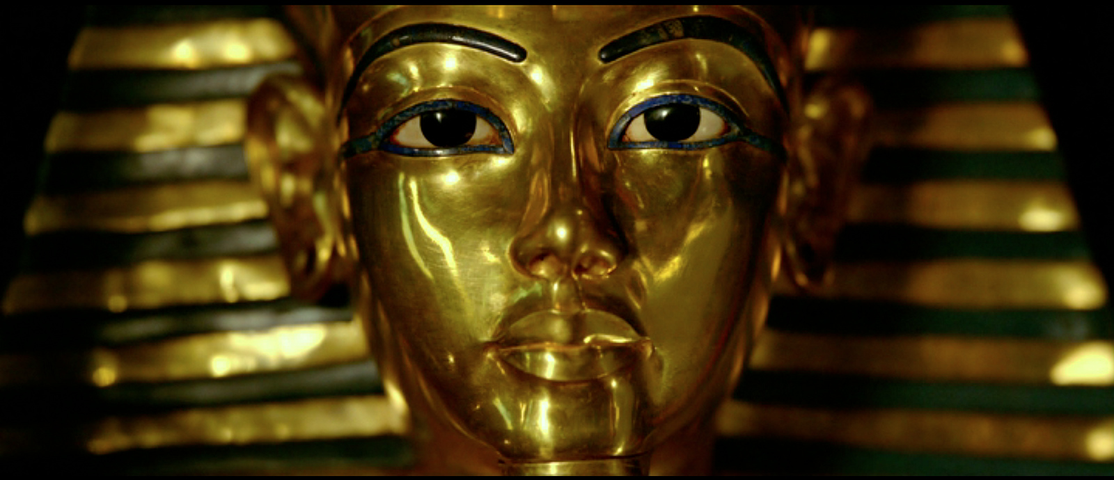 A close-up image of King Tutankhamen's burial mask. It is made out of gold. The only features on the face that are not gold are two thin black eyebrows and two large eyes with iris and pupils colored black.