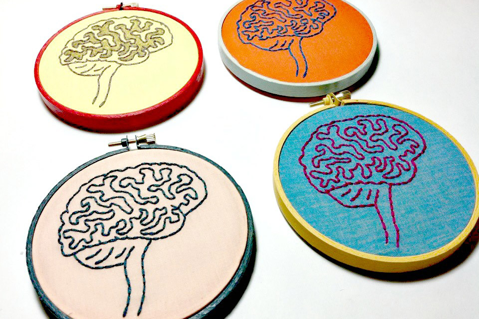 4 hand-stitched images of brains. The top left is yellow, the top right is orange, the lower right is bright blue, and the lower left is mauve.