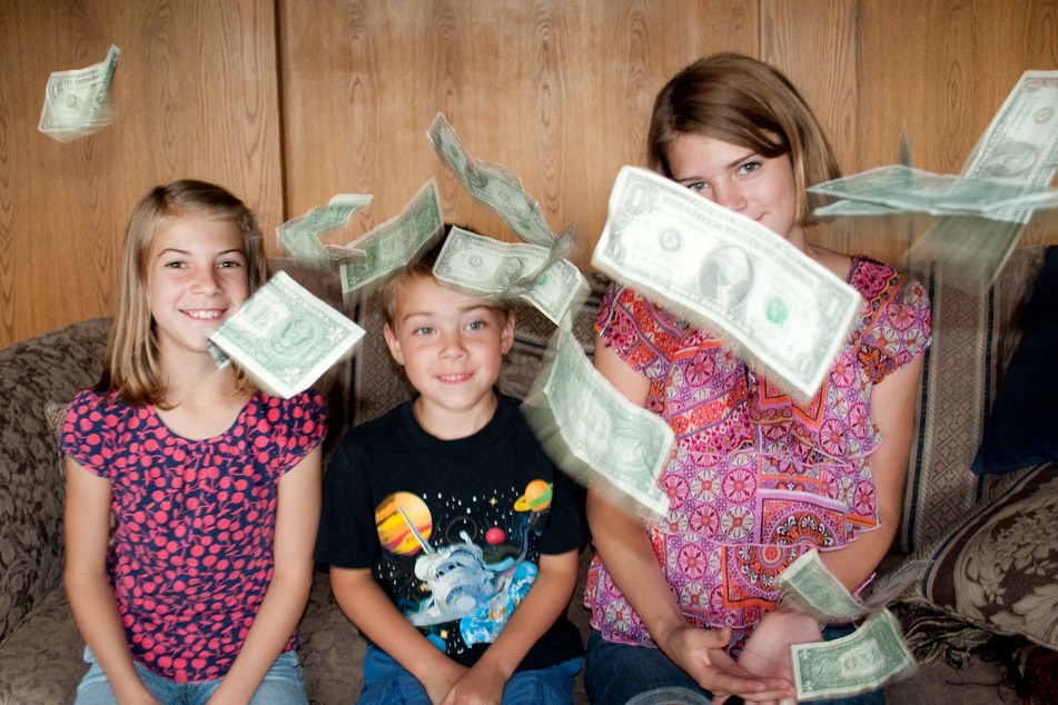 Three Caucasian children are sitting on a couch. In the foreground are dollar bills that it appears they have thrown.