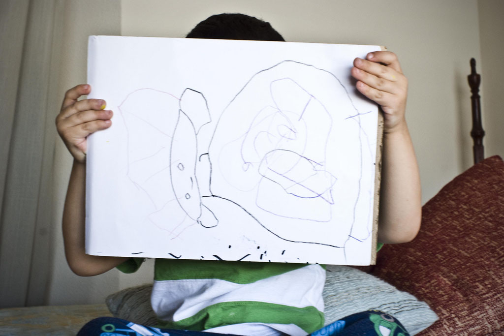 A child holding up a sideways image of a picture he has drawn. The child's face can't be seen. The drawing appears to be of a child or a blobby Prince Leia from Star Wars.