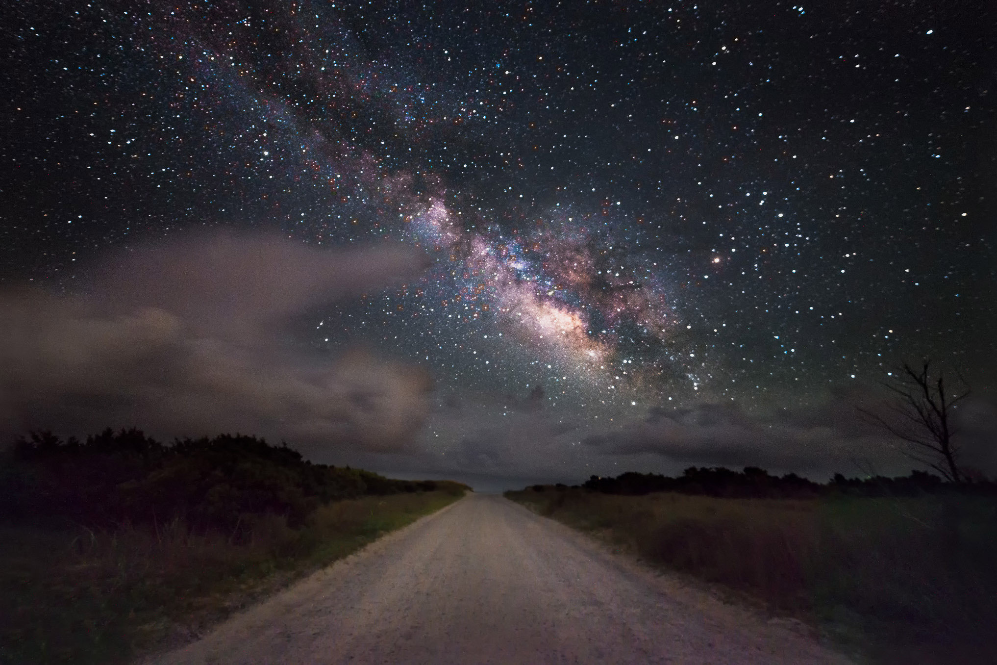 An image of a long dirt road. Above it is the night sky. On the left large white clouds are visible. On the right, the thousands of stars in the milky way.