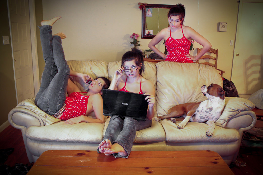A young woman sits on the couch with her legs in the air, next to a young woman who looks identical to her on a computer, and a brown and white dog sits next to that young woman. Behind the couch, another young woman, identical to the other two young women looks at the dog.