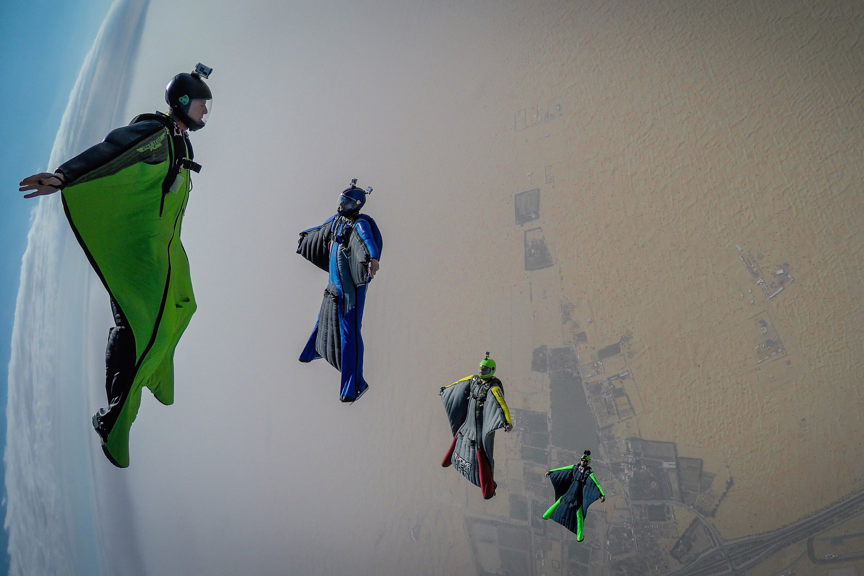 Four skydivers getting into formation over the Dubai Desert