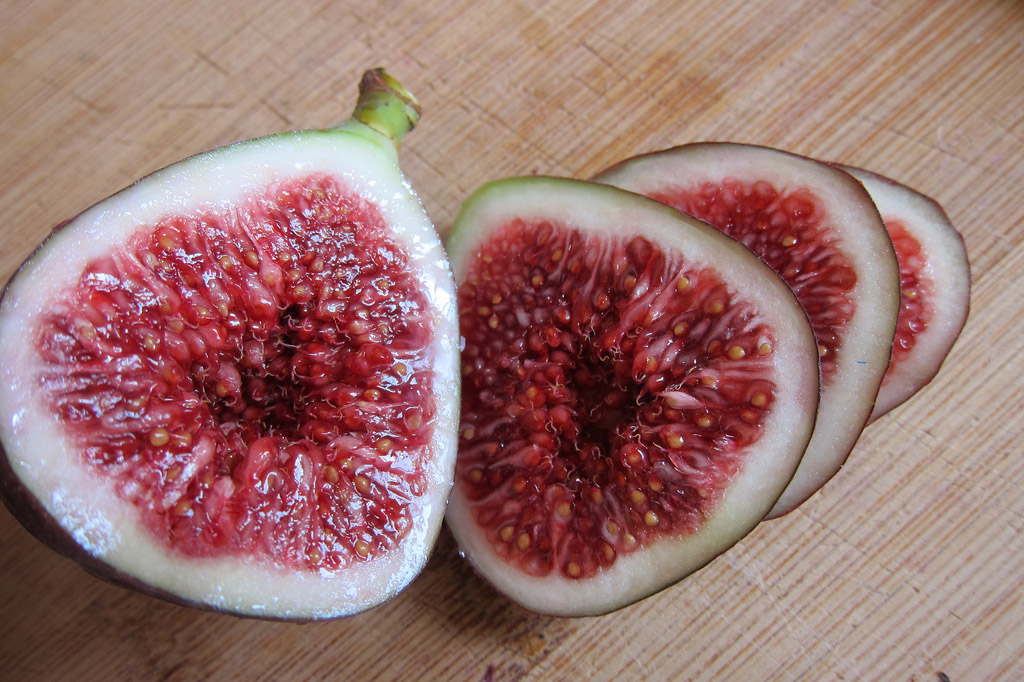Two figs cut in half. There is a small indentation in each visible fig center. The figs' insides are magenta-pink with a white layer surrounding them.