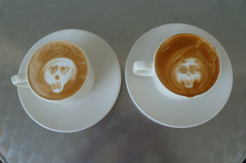 An overhead shot of two white coffee cups. The coffee cup on the left has white foam art in the shape of a skull. The skull's eyes are hearts. It's in the center of the cup with a light brown coffee background. The cup on the right also has  white skull as foam art. But its eyes are flat brown circles. The background is a darker brown.