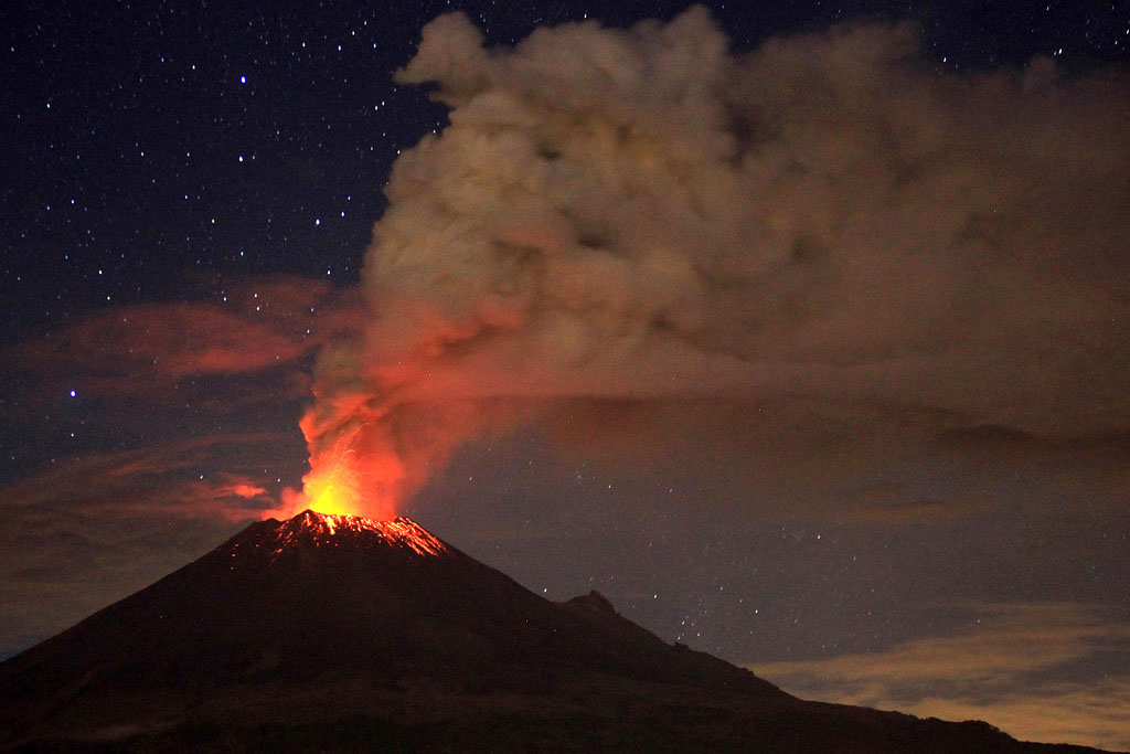 A volcano erupting in the night. The volcano is dark, but it's tip is bright red with lava. Gray smoke billows into the sky. In the background, night sky, stars, and clouds tinged pink from the lava's reflected light are visible.