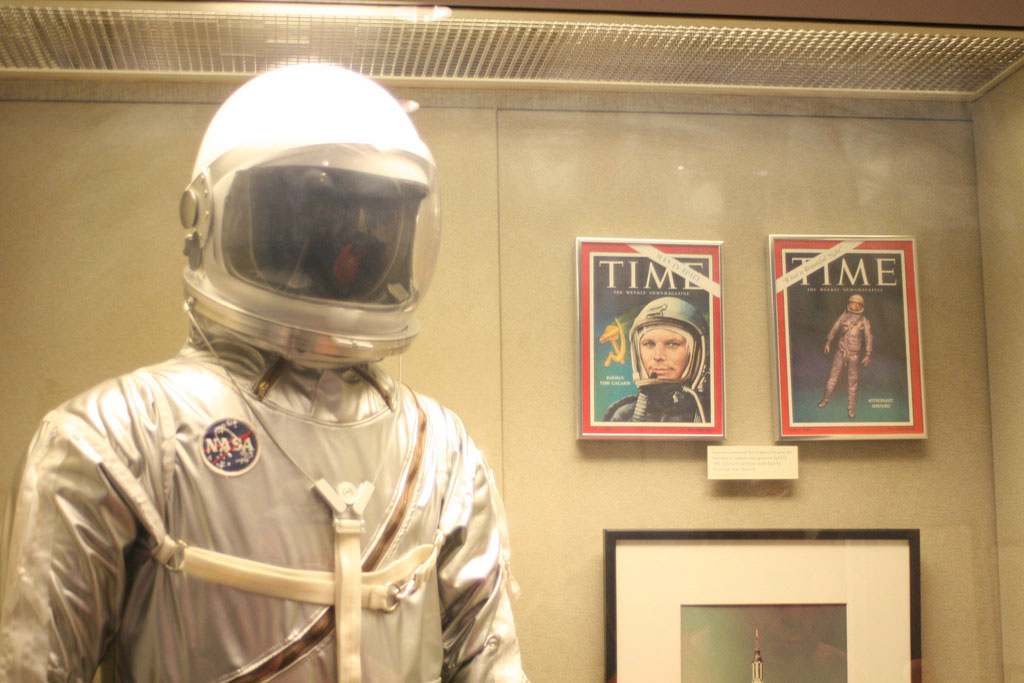 A museum display of John Glenn's spacesuit and magazine covers featuring him