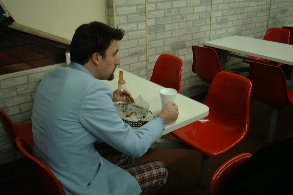 a man eating tacos alone