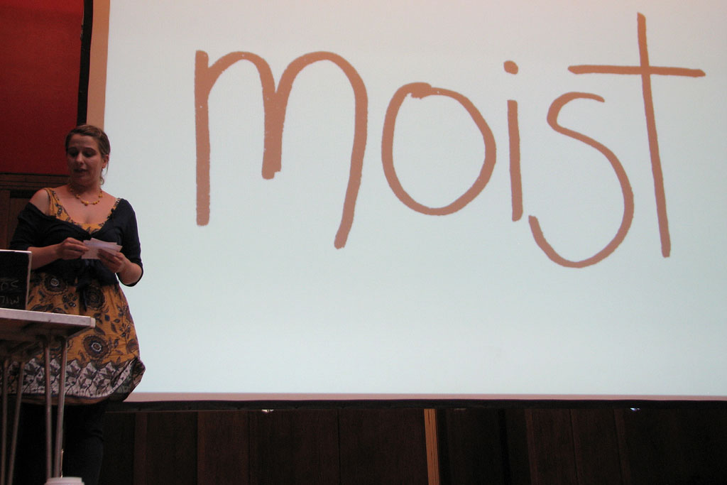 A woman next to a white board with the word moist written on it in big letters.