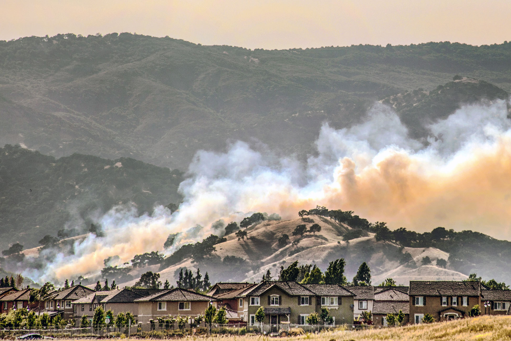 Smoke and mountains in the background, a neighborhood in the foreground.