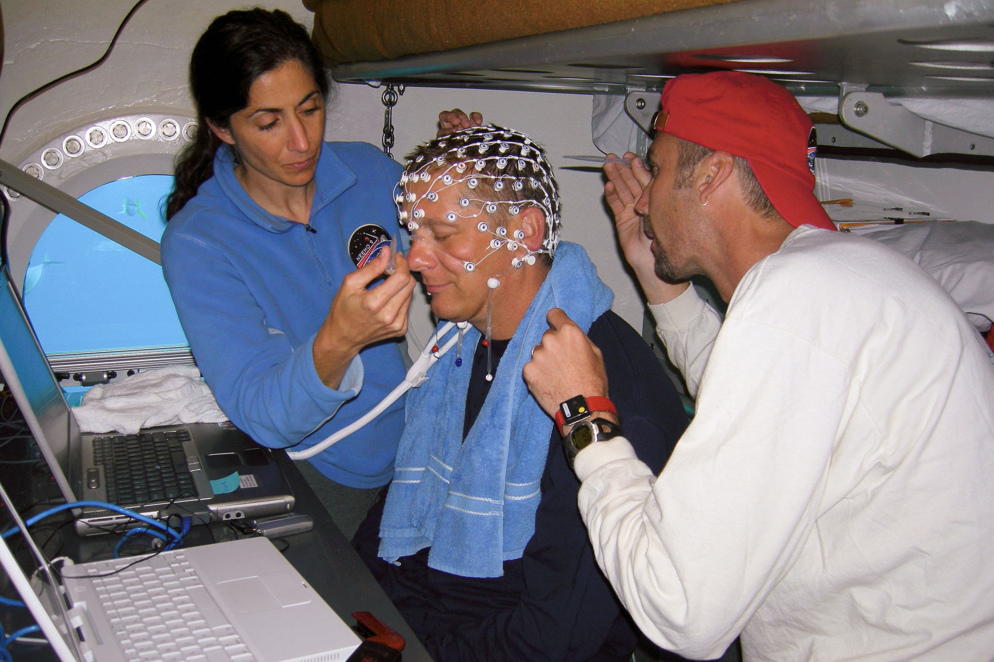 two people setting up an electroencephalogram cap on another person
