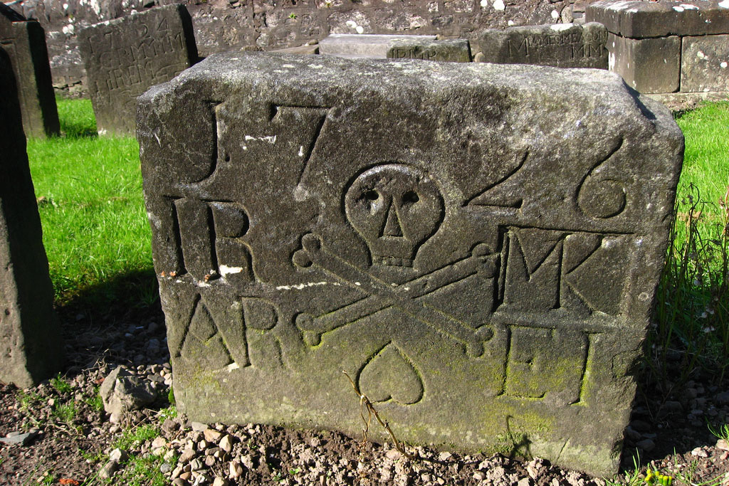 A very old gravestone with a detail of a skull and crossbones. More gravestones behind it.