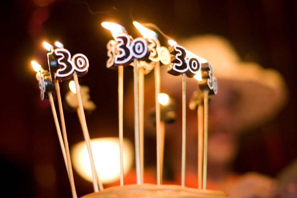 candles shaped like the number 30 that are lit