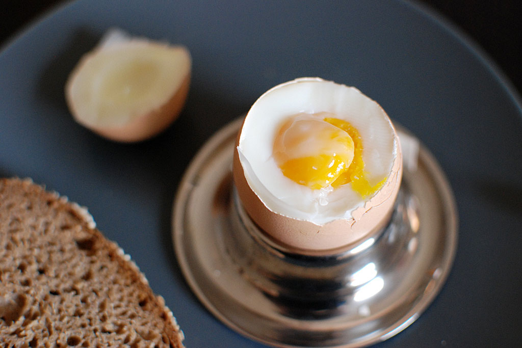 a soft boiled egg in a cup, and a piece of toast on a plate.