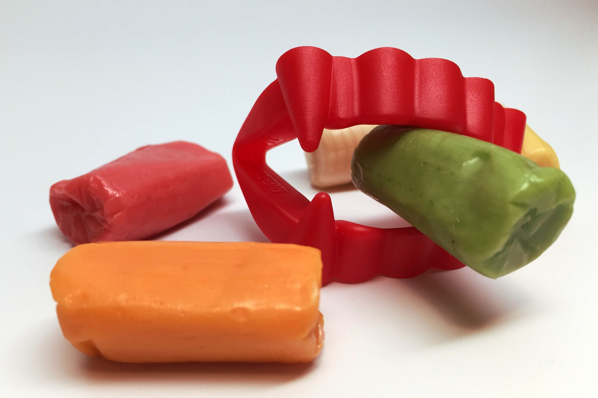 Red plastic vampire teeth and some candies. (NIAID, Flickr)