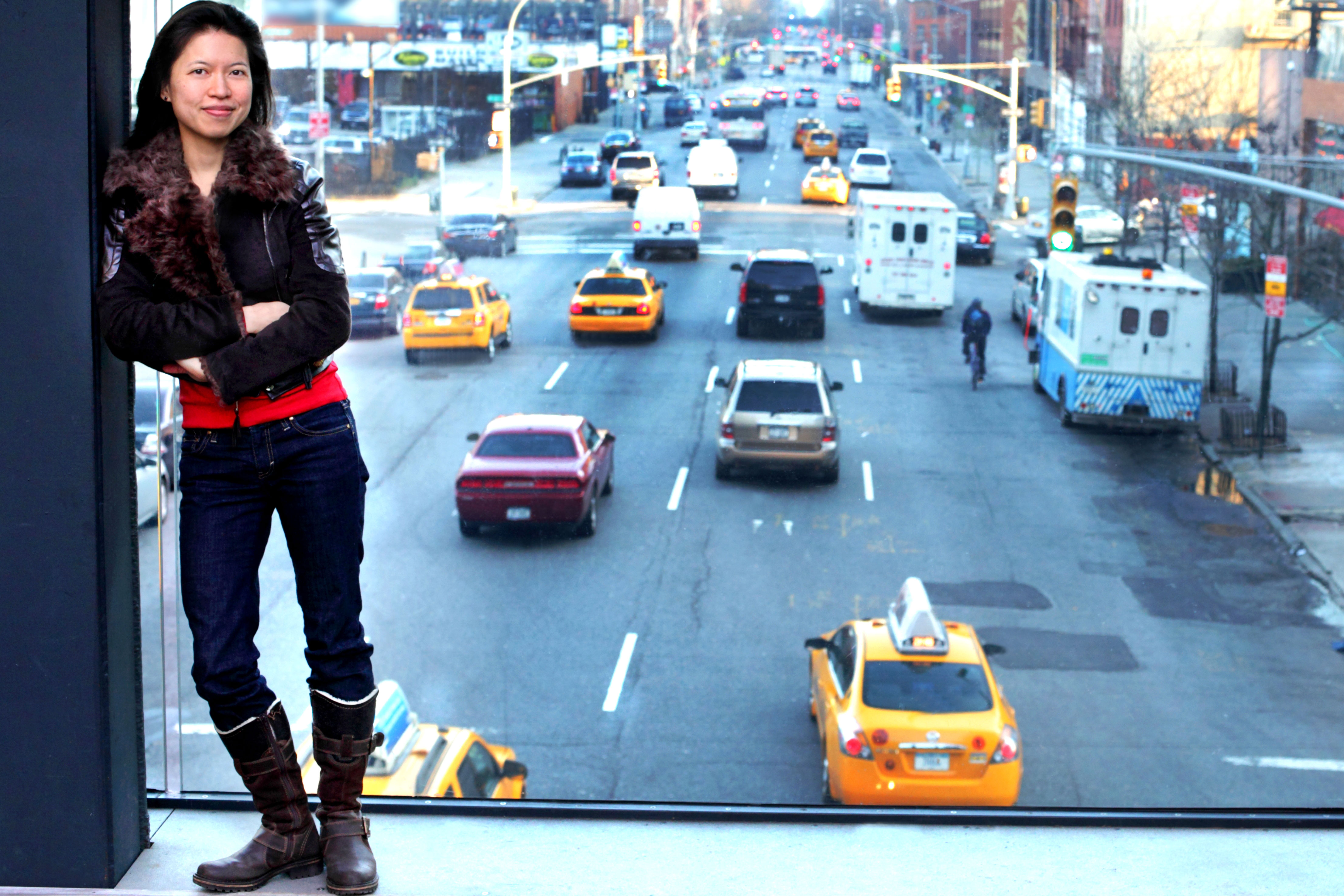 composer posing in a window overlooking NYC traffic