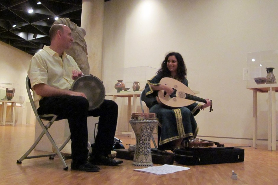 A man and woman smile at each other while playing Middle Eastern music in an Art Gallery