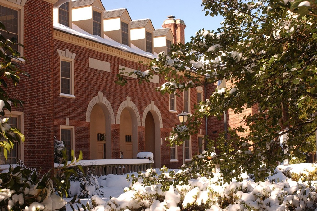 A brick building is surrounded by snow covered trees