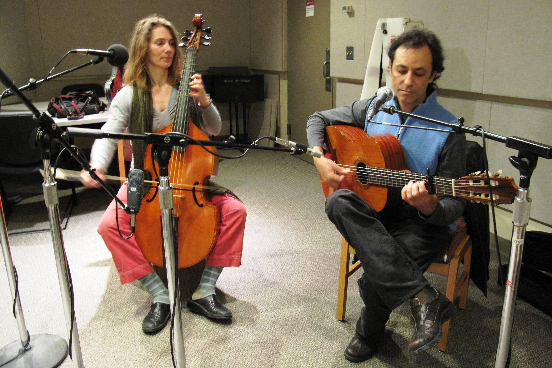 a woman plays a viola da gamba and a man plays a guitar