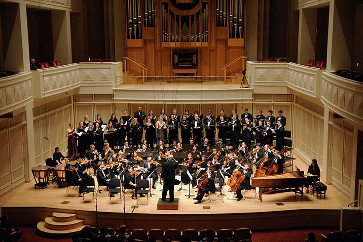 a chorus and orchestra perform on a dimly lit concert stage