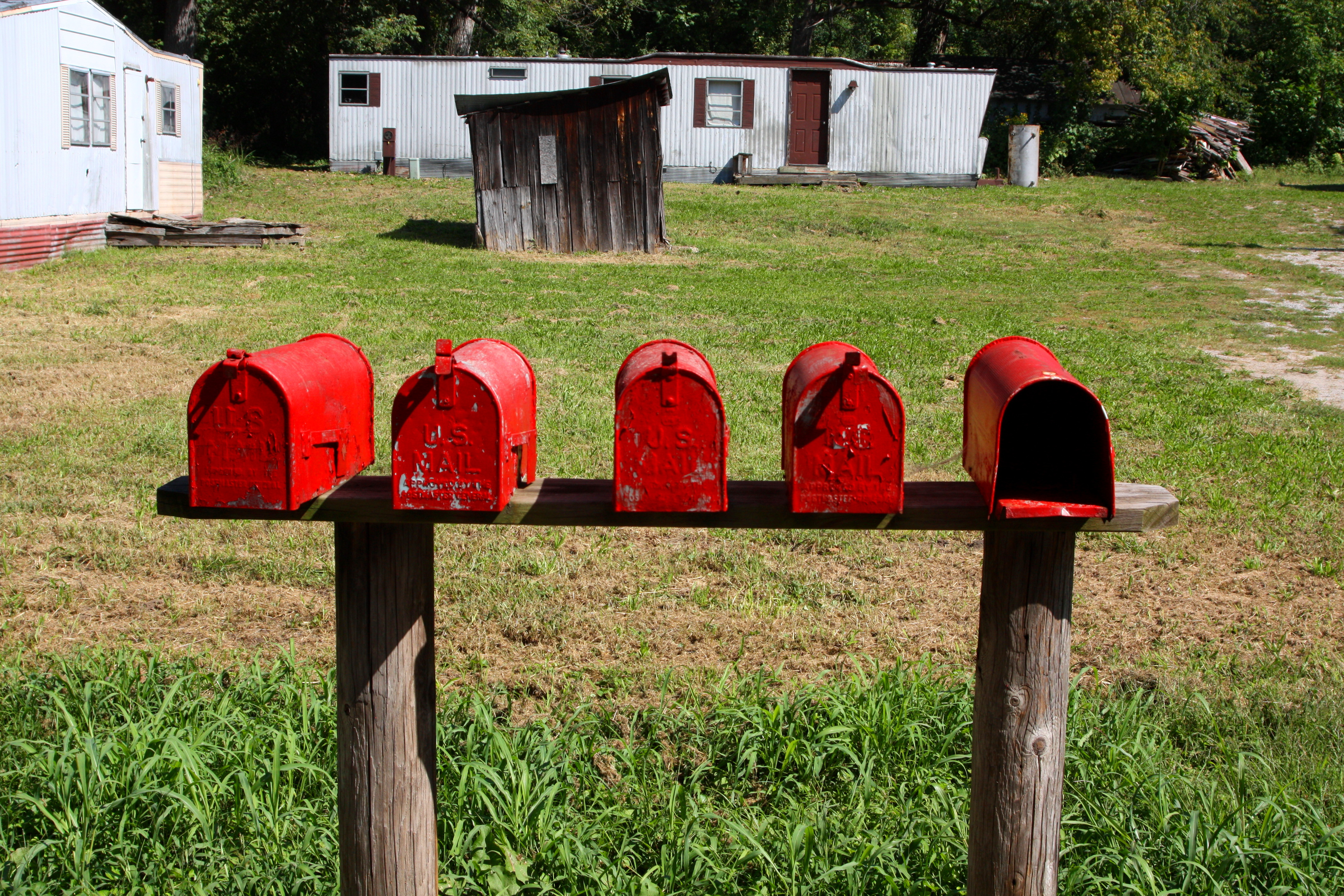 photo of five red mailboxes with trailers in background