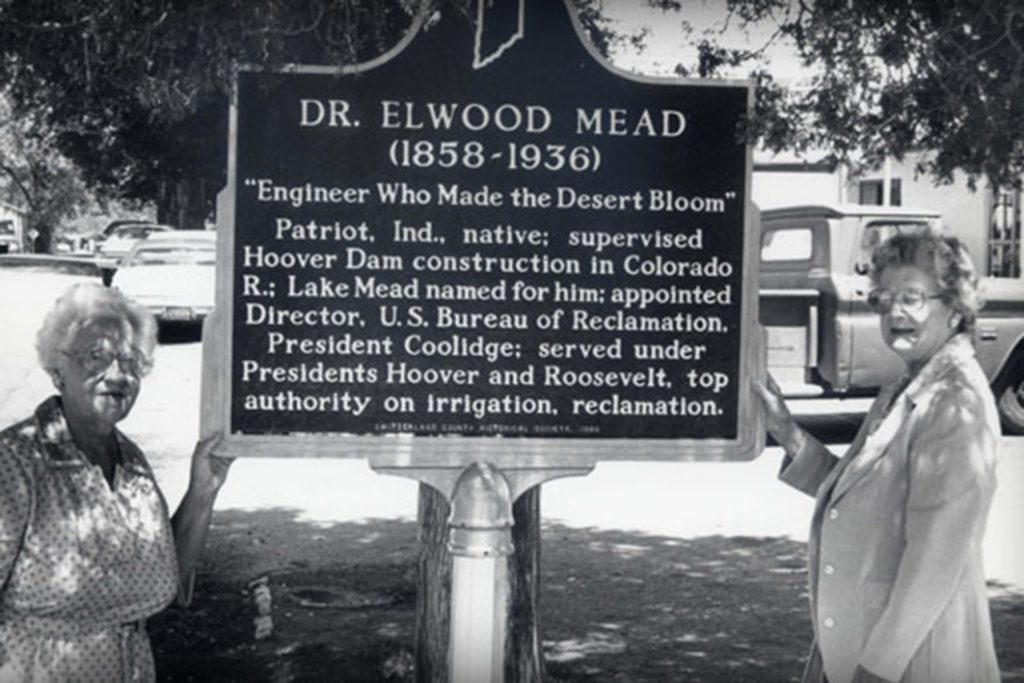 Two women stand by the Elwood Mead historical marker in Patriot, Indiana.
