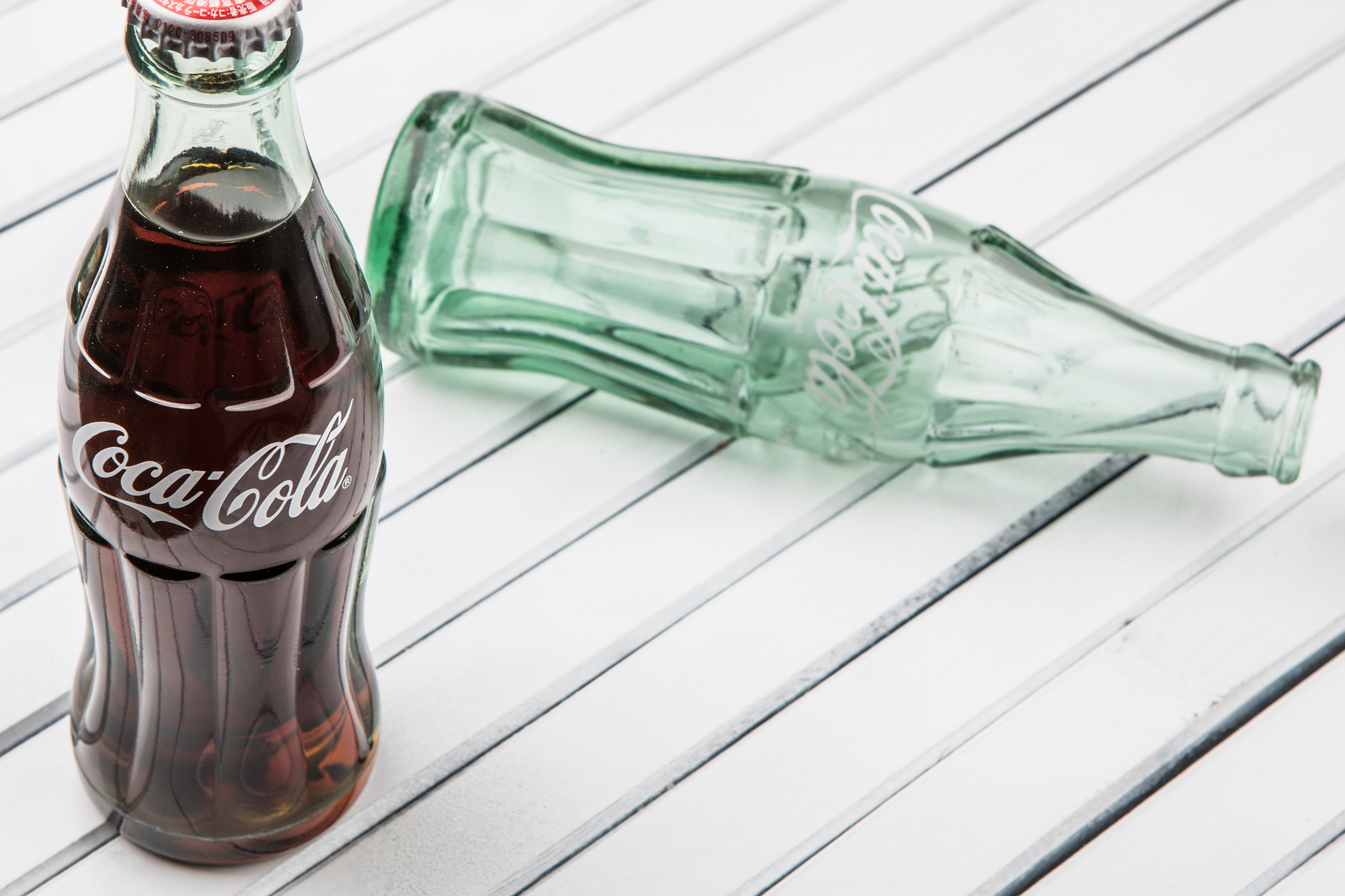 A full glass Coca-Cola bottle stands next to an empty green one.