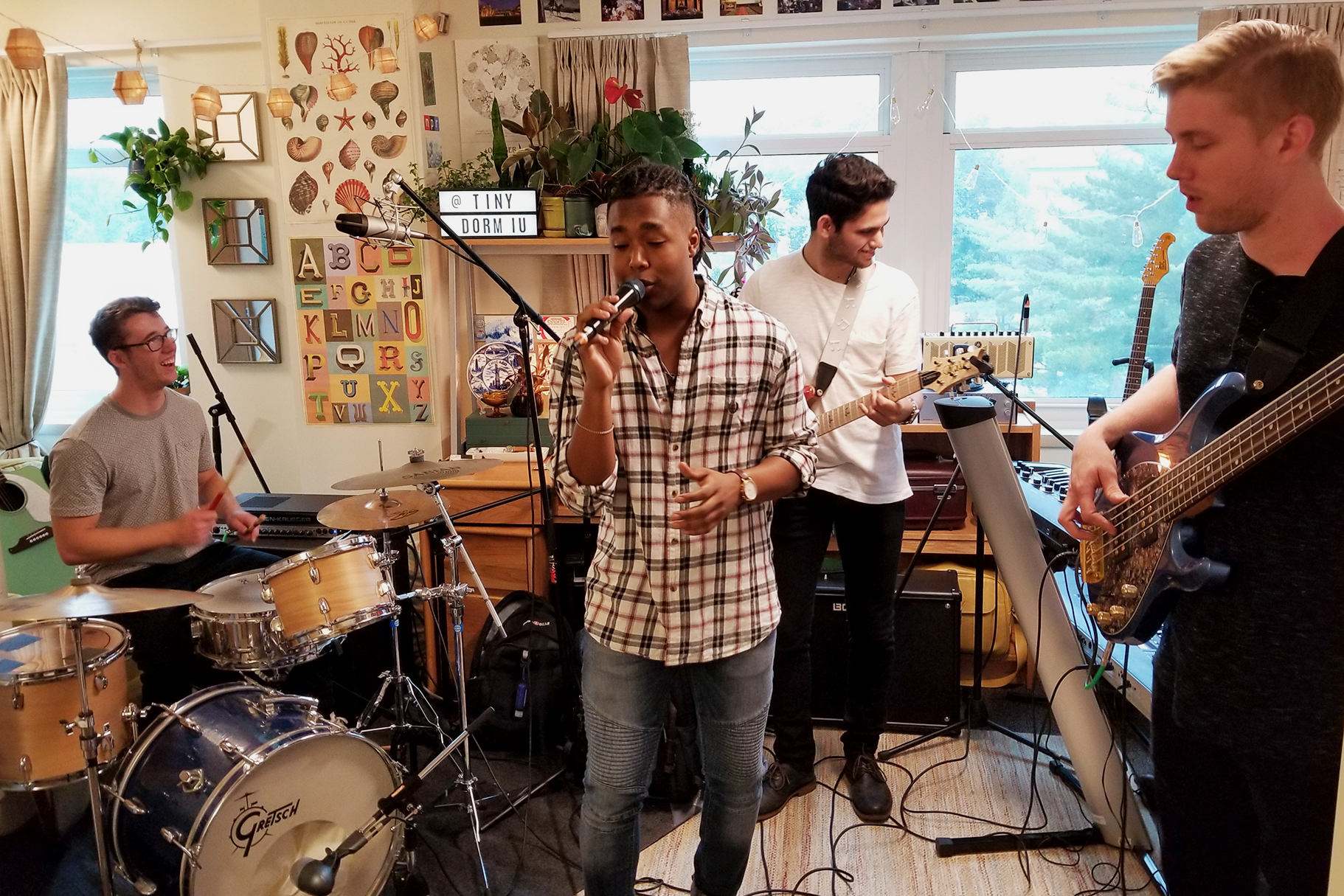 A drummer, singer, guitarist and bassist all pack into a dorm room to play music