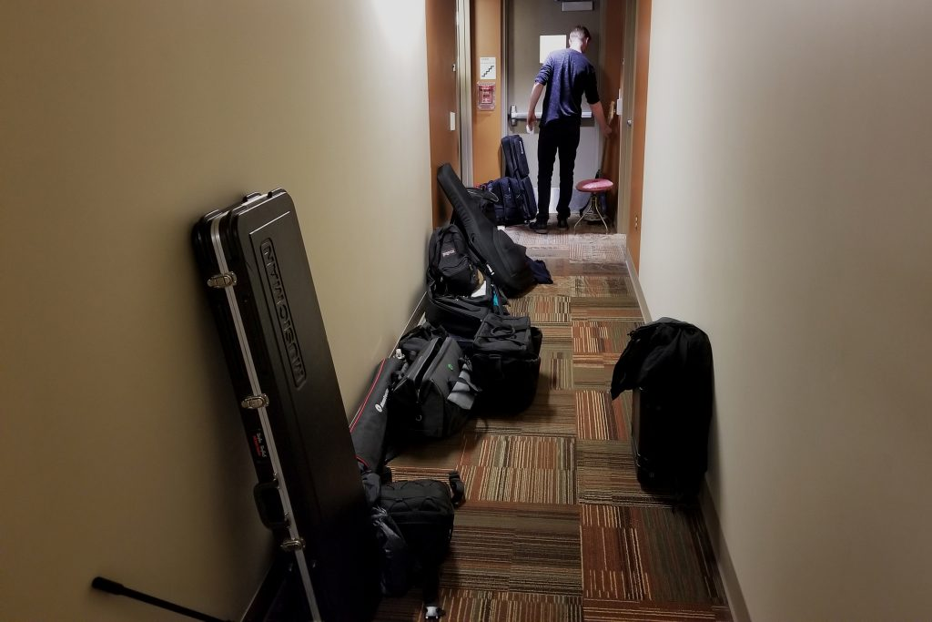 A tight hallway is packed with equipment cases just outside of the room where the concert happens.