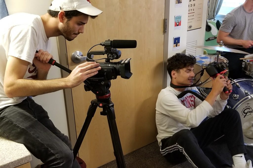 One videographer (left) sits on the edge of a sink while another sits on the floor to get a good shot.