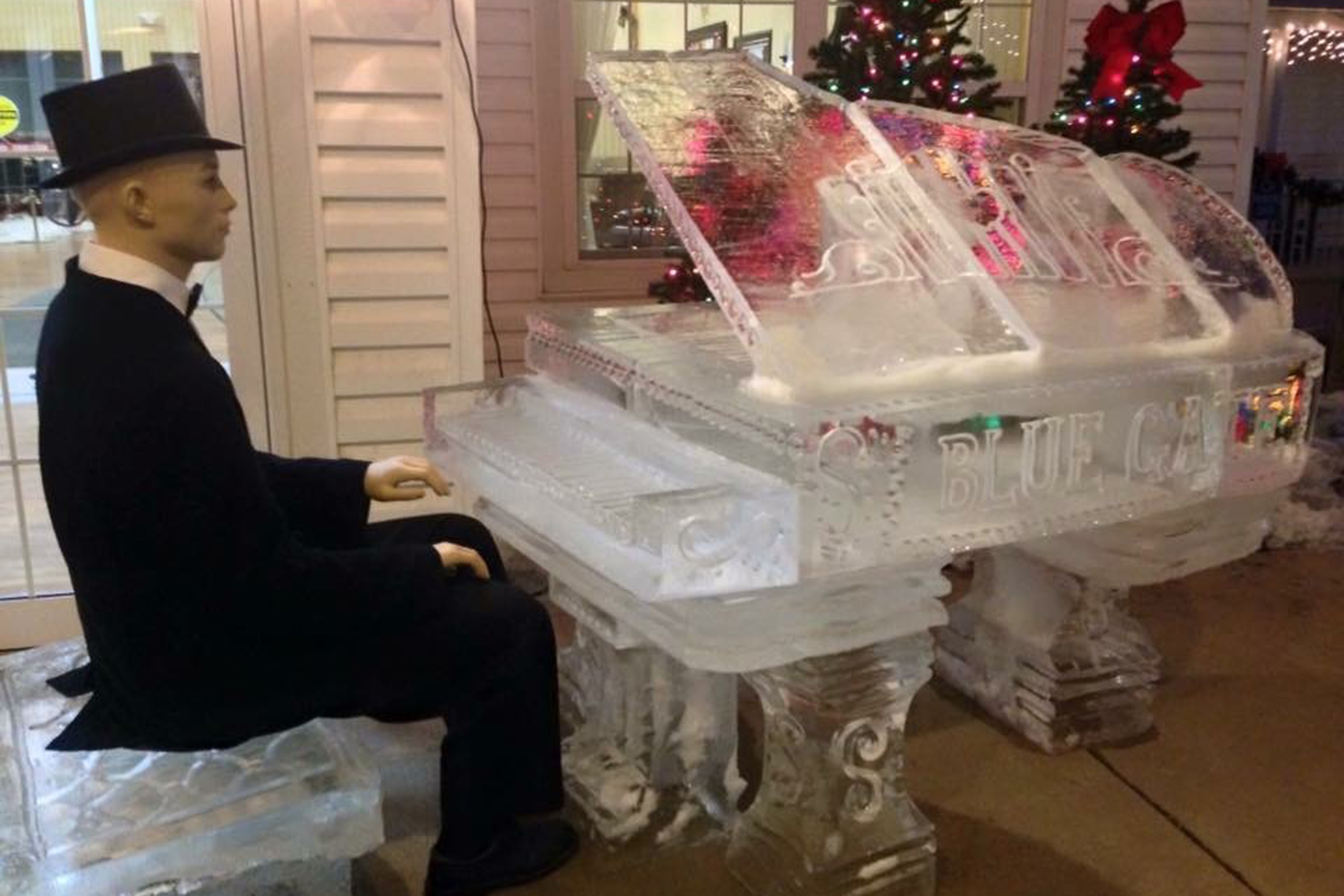 A mannequin sits at a grand piano made entirely out of ice.