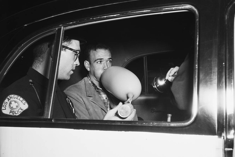 A cop (left) administers a drunkometer test to a man (right) in the back of a police car.